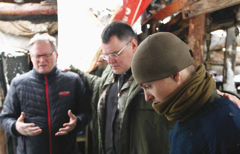 Military chaplain Gennady and Hannu pray with soldiers in a bunker in the war-zone. Gennady is pastor of the largest church in Mariupol. He also manages the Mariupol orphanage and children's home and facility for the disabled elderly. GCM Ministries financed a broiler farm for the children and adults in the war-zone, on a regular basis providing broilers to those in these shelters.