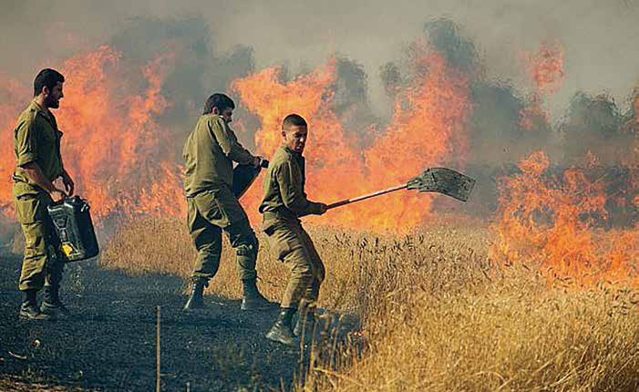 Soldiers battle flames that were started by hundreds of missiles fired from across the border in Gaza.